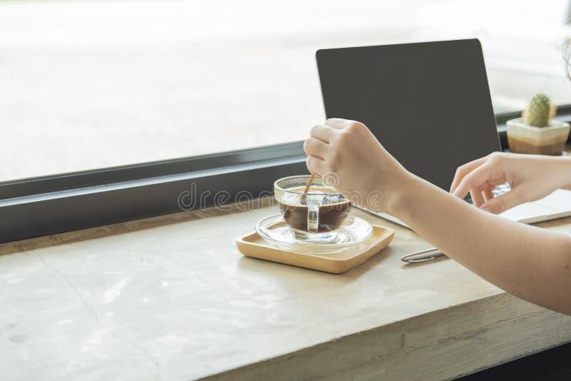Hand der Frauenmischungsschale heißen schwarzen Kaffees bei der Anwendung des Laptops E-Commerce, Hochschulausbildung, Internet-T lizenzfreies stockfoto