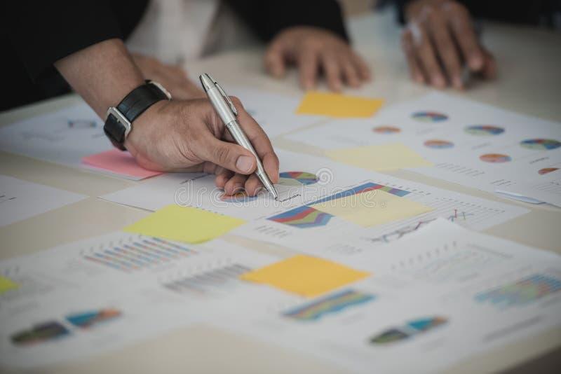 Hand der Geschäftsmannfunktion schreiben mit einem Stift auf Daten-Diagramme, docu stockfotos