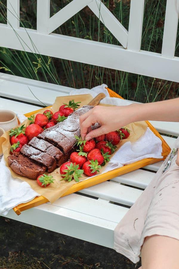 Hand der jungen Frau, die für einen Behälter mit selbst gemachtem Kuchen und frischen Erdbeeren erreicht stockbilder