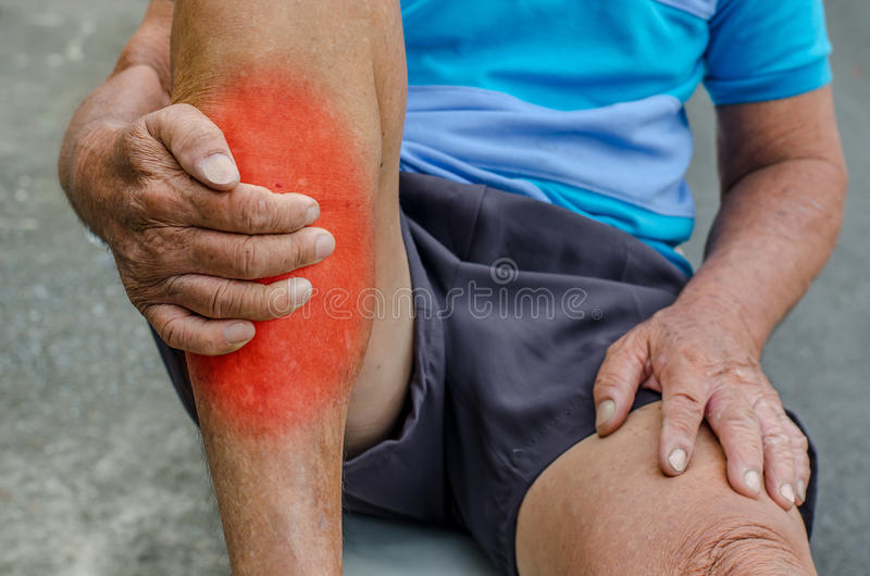 Hand des älteren Mannes, die Fuß hält und Knöchel im Schmerzbereich massiert stockfotografie