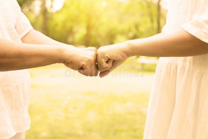 Hand des asiatischen Frauenseniors, der morgens den Handjungen Frauen Fauststo? an im Freien, geerntetes Bild gibt stockbilder