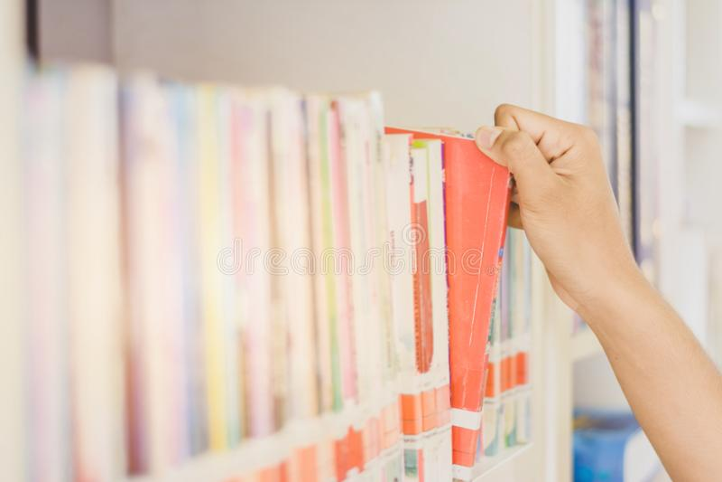 Hand des asiatischen Studenten ein Buch für das Ablesen in College libr auswählend stockfotografie