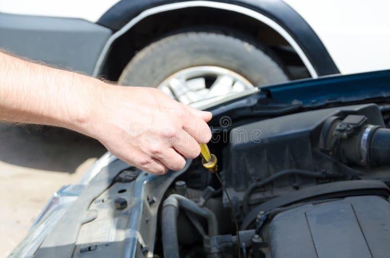 Hand des Automechanikers mit einem Werkzeug Ölstand überprüfend lizenzfreies stockfoto