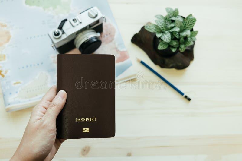 Hand des Frauengriffpasses hat Retro- Kamera, Weltkarte, Bleistift, lizenzfreie stockfotos