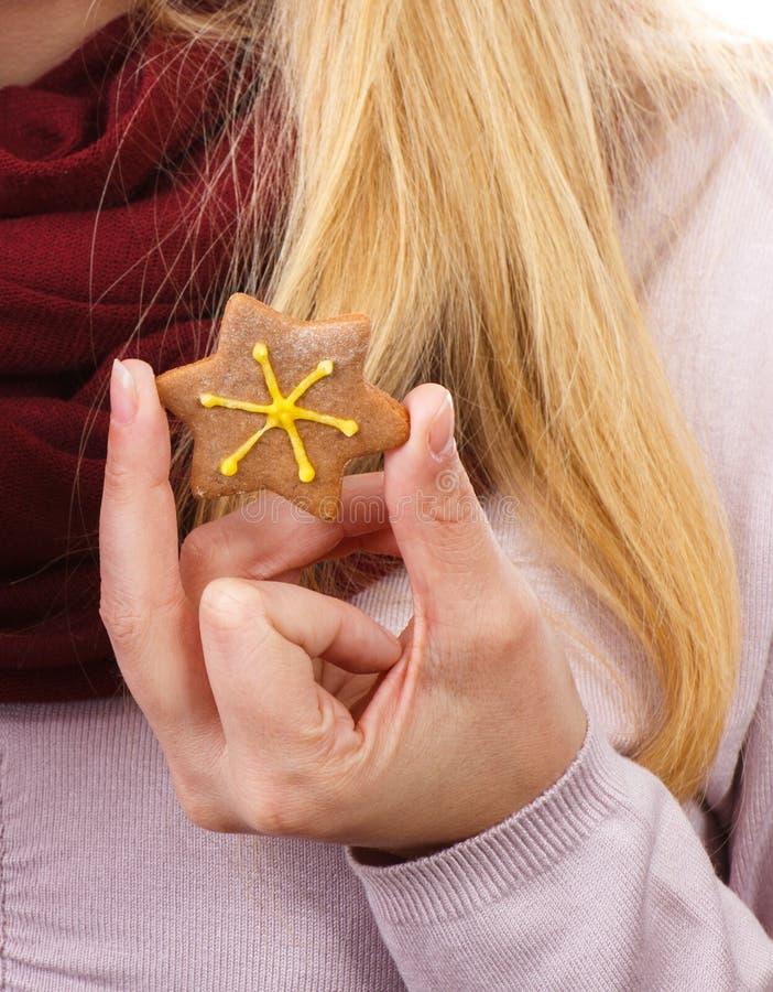 Hand des Frauenholdinglebkuchens in Form des Sternes, Weihnachtszeit stockfoto