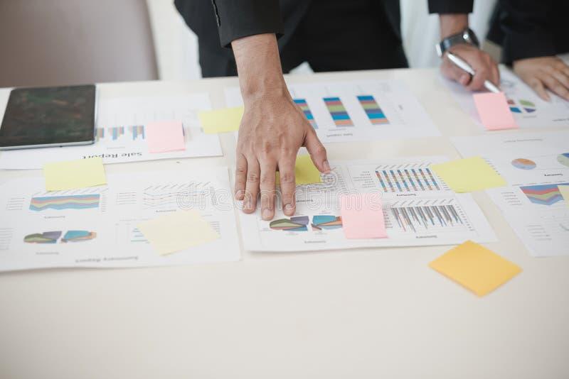 Hand des Geschäftsmannes arbeitend an Daten-Diagrammen, Dokument in Büro d lizenzfreie stockfotografie