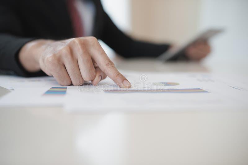 Hand des Geschäftsmannes arbeitend an Daten-Diagrammen und Digital-Tablet an stockfotografie