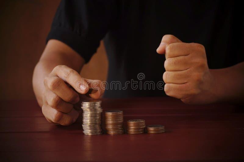 Hand des Geschäftsmannes steckte Geld auf Stapel von Münzen lizenzfreies stockfoto