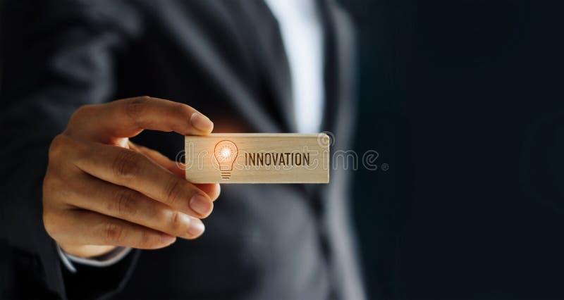 Hand des Geschäftsmannholdingikonen-Glühlampenglühens und des Innovationswortes im hölzernen Block, Symbol, Network Connection lizenzfreie stockfotos