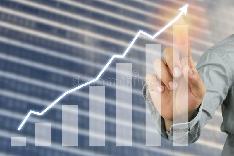 Hand des Geschäftsmannpunktes zur Spitze des Balkendiagramms und des Wolkenkratzers stockbild