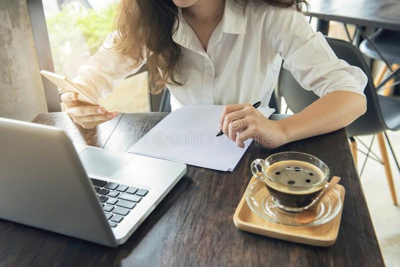 Hand des intelligenten Handyblickes des asiatischen Frauengebrauches auf Mobile und Papier für Anmerkung vorbereiten E-Commerce,  lizenzfreies stockbild