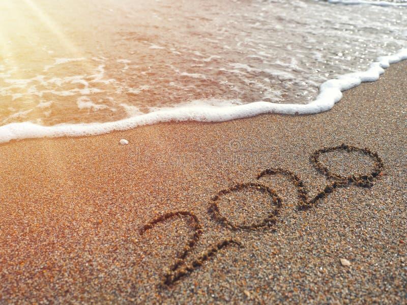 Hand des Jahres 2020 geschrieben auf sandigen Strand in warmen Blendenfleck des Sonnenuntergangs stockfotografie