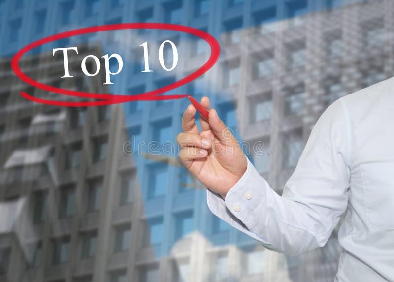 Hand des jungen Geschäftsmannes schreiben das Wort Top 10 auf Wolkenkratzer lizenzfreie stockfotos
