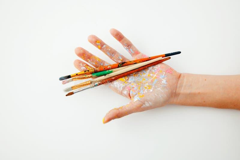 Hand des Künstlerholdingsatzes Pinsel auf weißem Hintergrund mit Raum für Text Lokalisiertes Bild lizenzfreie stockfotografie