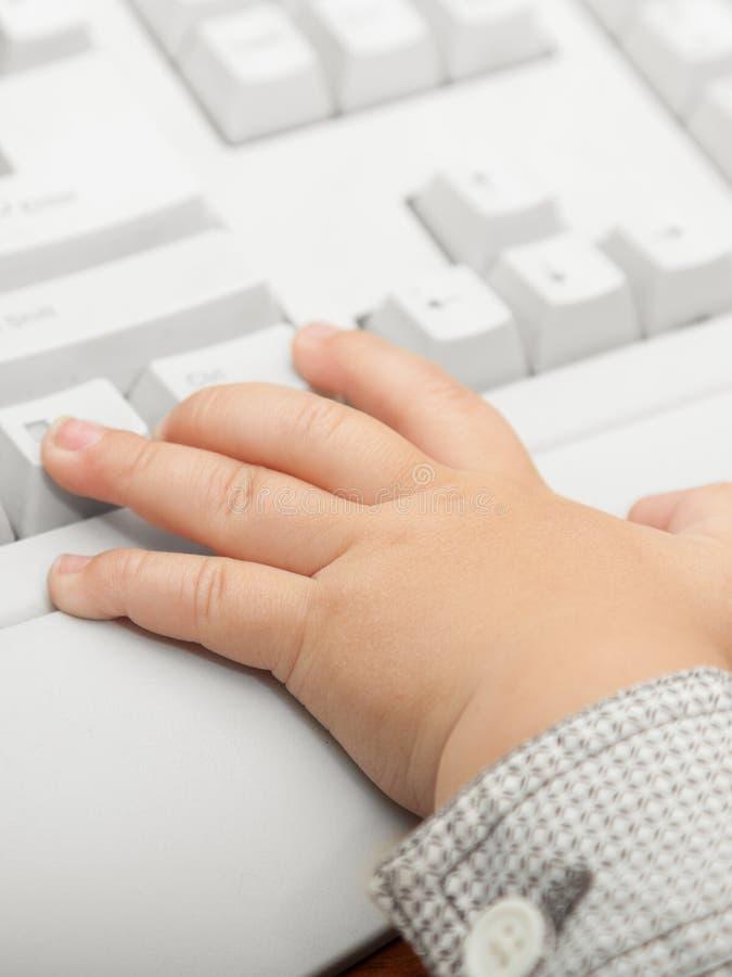 Hand des Kindes des kleinen Jungen Kinderauf der Computertastatur lizenzfreie stockfotos