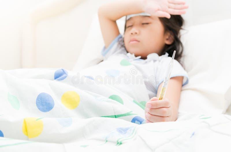 Hand des kleinen Mädchens mit einem Thermometer stockbilder