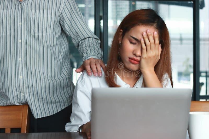 Hand des Kollegen die deprimierte traurige Asiatin mit den Händen auf Gesicht tröstend schreiend im Büro lizenzfreies stockfoto