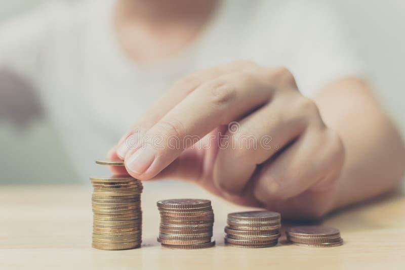 Hand des männlichen setzenden Goldmünzestapels, der Finanzierung und der Investition SAV stockbilder