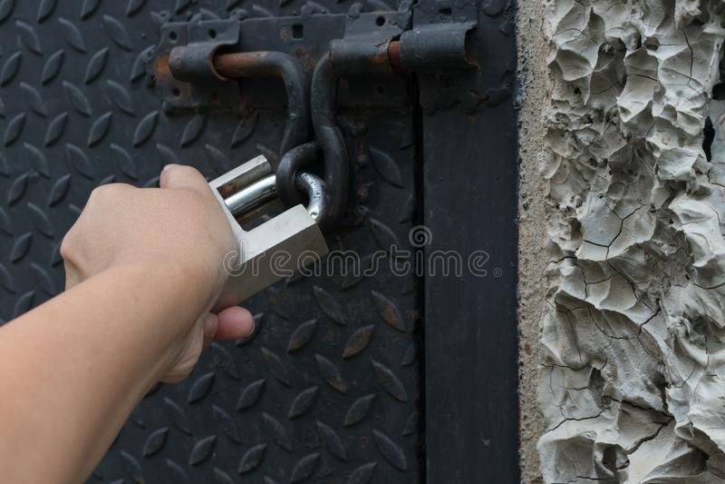 Hand des Mannes, der ein Metallvorhängeschloß hält, dem mit umklammert wird stockfoto
