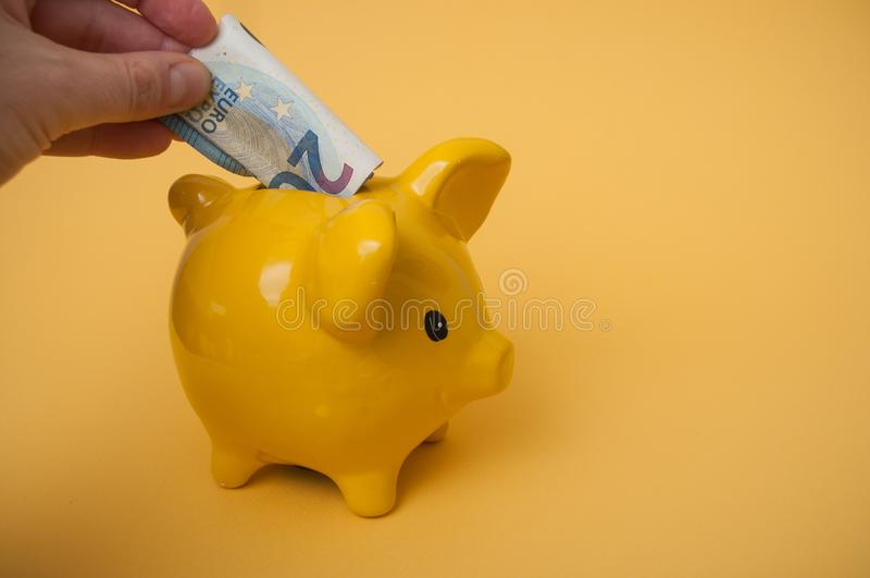 Hand des Mannes die zwanzig-Euro-Banknote in gelbes Sparschwein auf gelbem Hintergrund einsetzend lizenzfreies stockbild