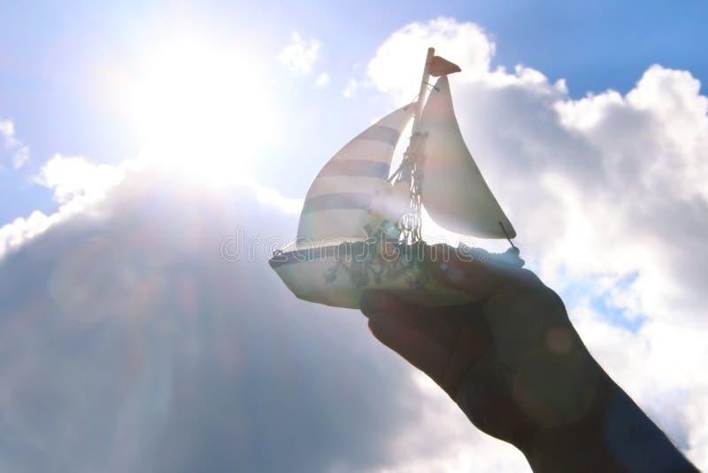 Hand des Mannes ein handgemachtes Schiff auf dem Himmel halten stockbild