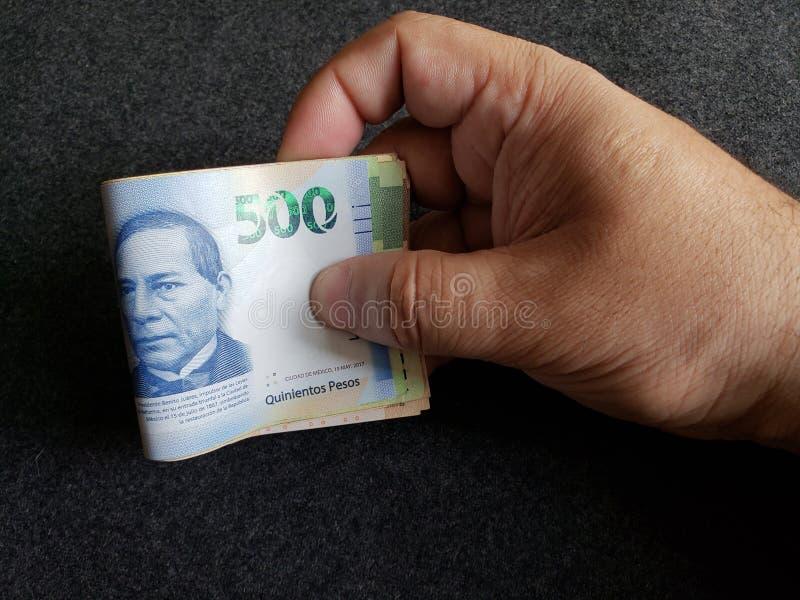 Hand des Mannes mexikanische Banknoten von 500 Pesos und von anderen Bezeichnungen halten stockbild