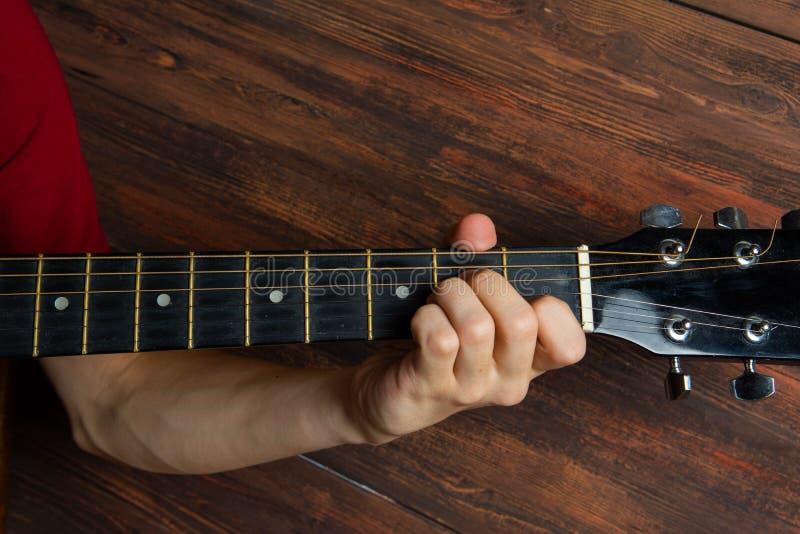 Hand des Mannes Sechsschnurgitarre auf hölzernem Hintergrund spielend Schablone für Konzertplakat lizenzfreie stockfotografie