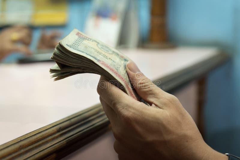Hand des nepalesischen Geldes des Manngriffs nach changemoney am Austausch MO lizenzfreie stockfotografie