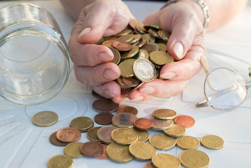 Hand des Pension?rs mit M?nzen und Einsparungen lizenzfreie stockfotografie