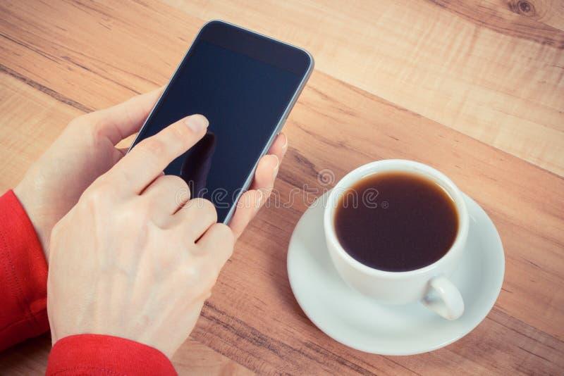 Hand des rührenden leeren Bildschirms der Frau des Handys, Tasse Kaffee stockfotografie