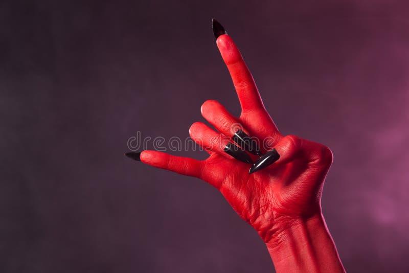 Hand des roten Teufels mit schwarzen Nägeln, Schwermetallgeste stockbilder