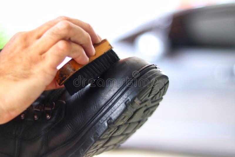 Hand des sauberen schwarzen Schuhes des Mannes mit Unschärfehintergrund lizenzfreies stockbild