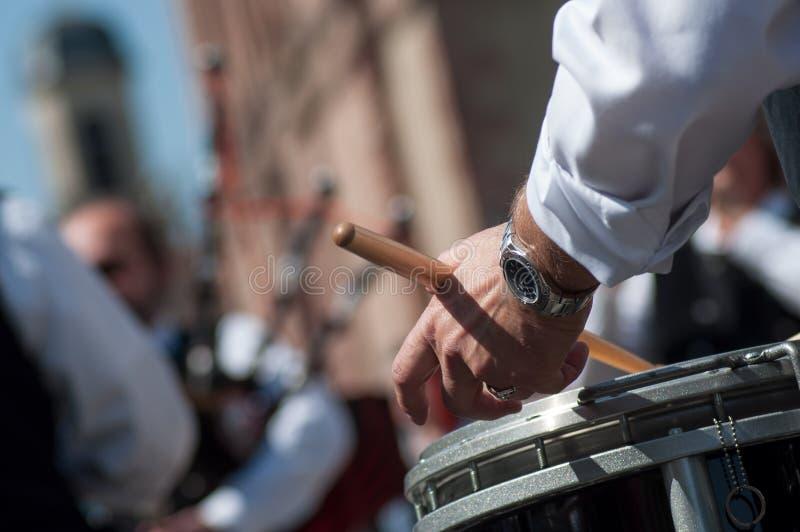 Hand des Schlagzeugers in der schottischen Band, die in der Straße spielt lizenzfreies stockbild