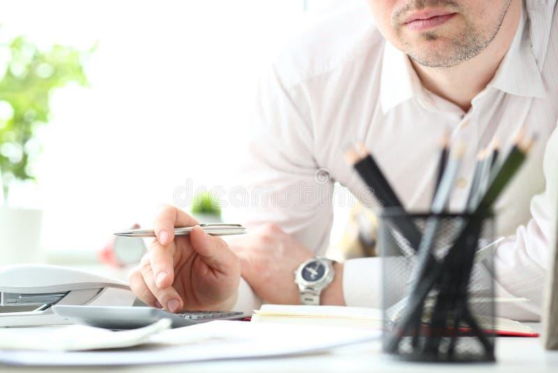 Hand des silbernen Stiftes des männlichen Sekretärsgriffs unter Verwendung des Taschenrechners stockbild