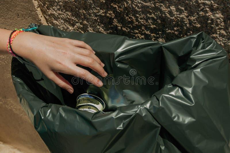Hand des werfenden Abfalls des Mädchens in einem Abfalleimer in Mérida lizenzfreies stockfoto