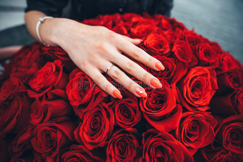 hand with diamond ring on the red roses stock photos
