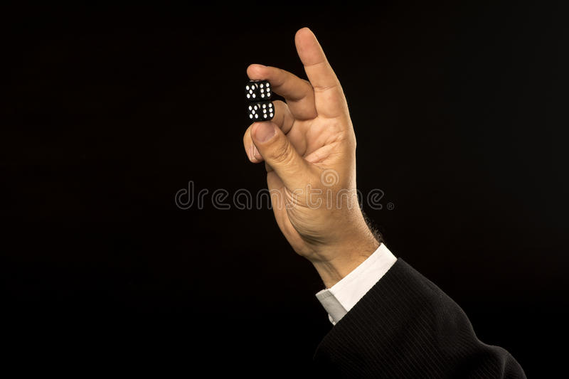 Hand with dices on black stock images
