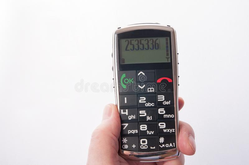 Hand, die älteres Mobil-pohne lokalisiert auf Weiß hält stockbilder