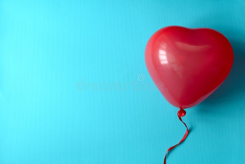 Hand, die Ballone eines rote Herzens auf blauem Papierhintergrund hält Valentinstag- oder Geburtstagsfeierkonzept lizenzfreie stockbilder