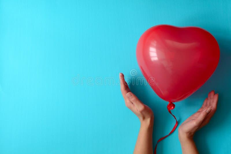 Hand, die Ballone eines rote Herzens auf blauem Papierhintergrund hält Valentinstag- oder Geburtstagsfeierkonzept lizenzfreies stockfoto