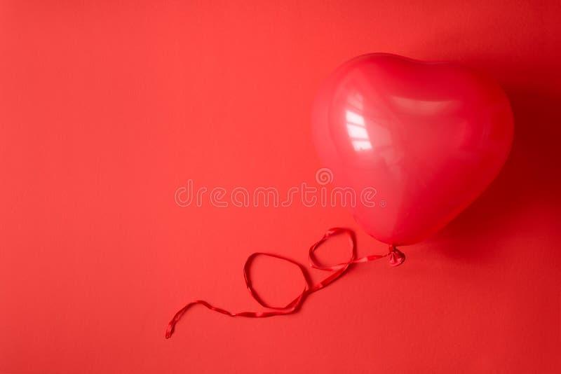 Hand, die Ballone eines rote Herzens auf rotem Papierhintergrund hält Valentinstag- oder Geburtstagsfeierkonzept stockfoto