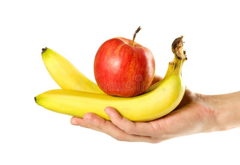Hand, die Bananen und roten Apfel hält Abschluss oben Getrennt auf wei?em Hintergrund lizenzfreie stockbilder