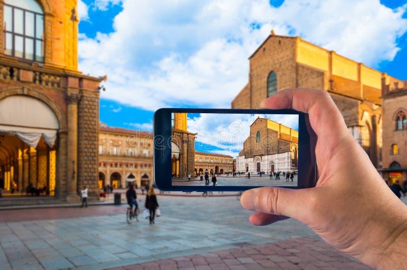 Hand die beeld met een smartphone in Bologna, Piazza Maggiore nemen stock foto