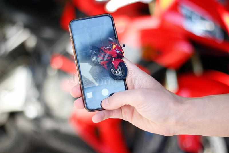 Hand die beelden op de sporten nemen van de telefooncamera rode motorfiets stock afbeelding