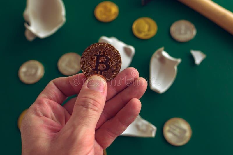 Hand die Bitcoin van gebroken piggy muntstukbank nemen royalty-vrije stock fotografie