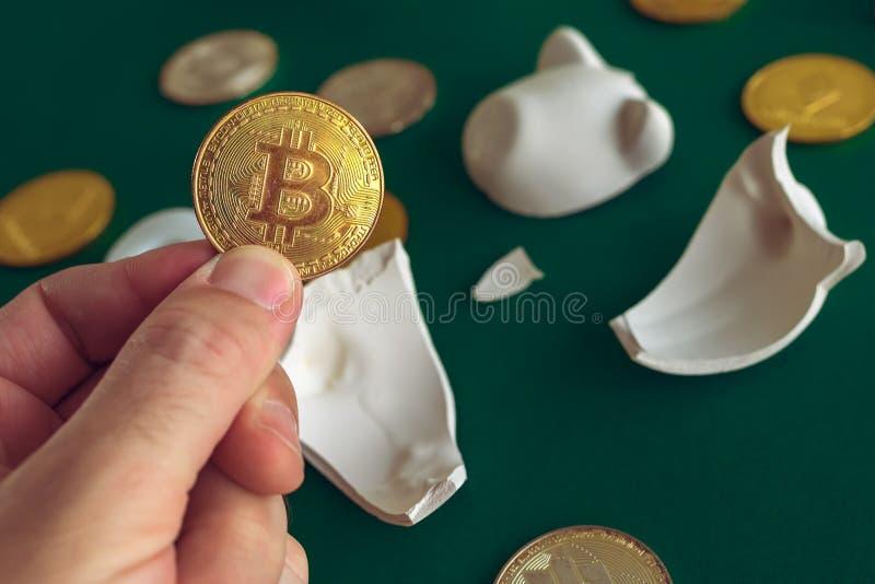 Hand die Bitcoin van gebroken piggy muntstukbank nemen royalty-vrije stock foto's