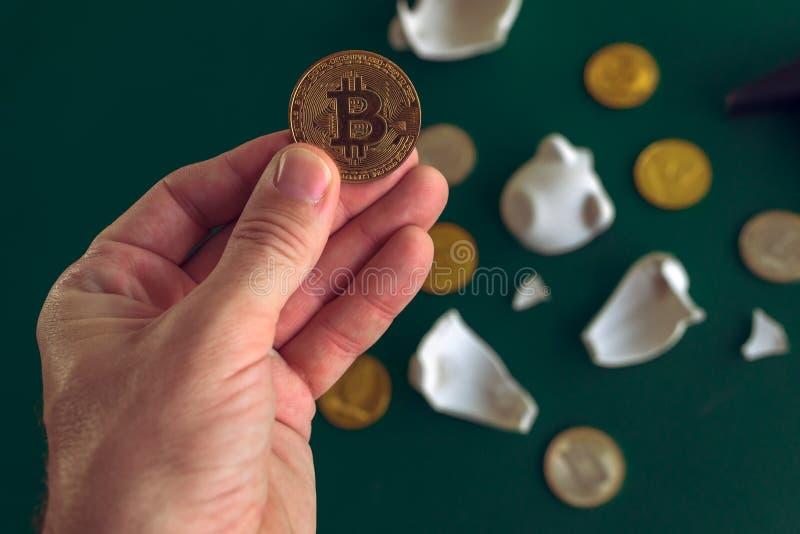 Hand die Bitcoin van gebroken piggy muntstukbank nemen stock afbeeldingen