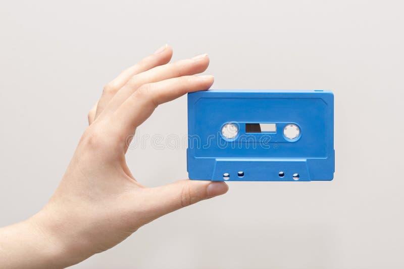 Hand, die blaue Kassette hält lizenzfreies stockbild