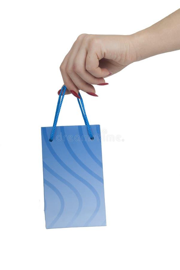 Hand, die blauen Geschenkbeutel anhält stockfotos