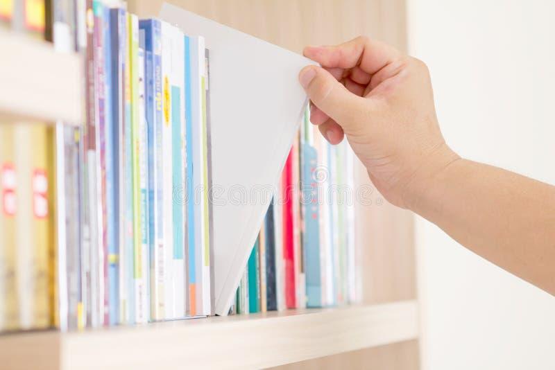 Hand die boek van boekenrek selecteren royalty-vrije stock foto's